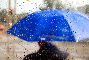 A man holding a blue umbrella during a rainy day