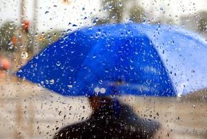 A man holding a blue umbrella during a rainy day