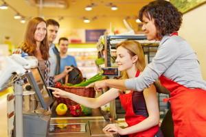 Ältere Verkäufer hilft einer neuen Kassiererin an der Kasse im Supermarkt